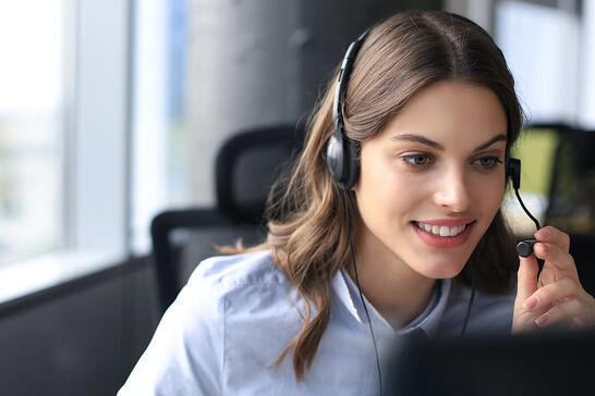 A customer service agent takes a call on a headset