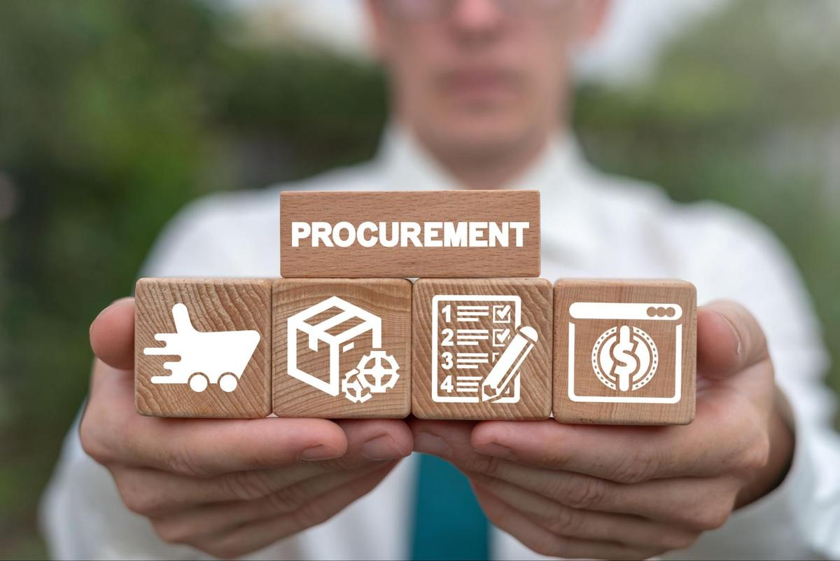 A man holds wooden blocks with procurement icons on them