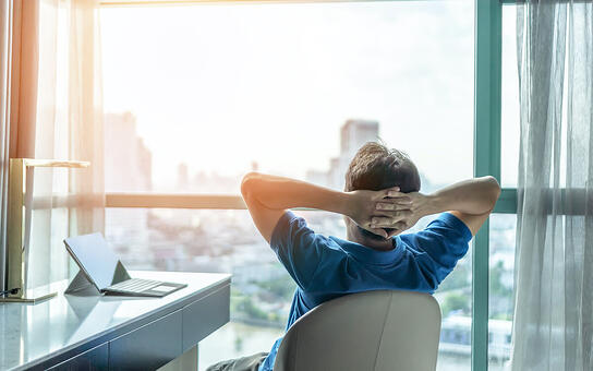 SaaS agreement: A man relaxes in his desk chair and looks out his office window