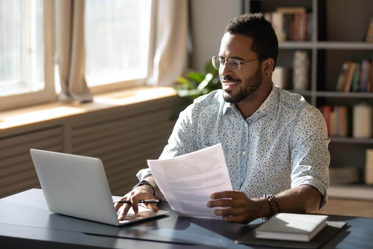 A man uses a laptop while holding paperwork