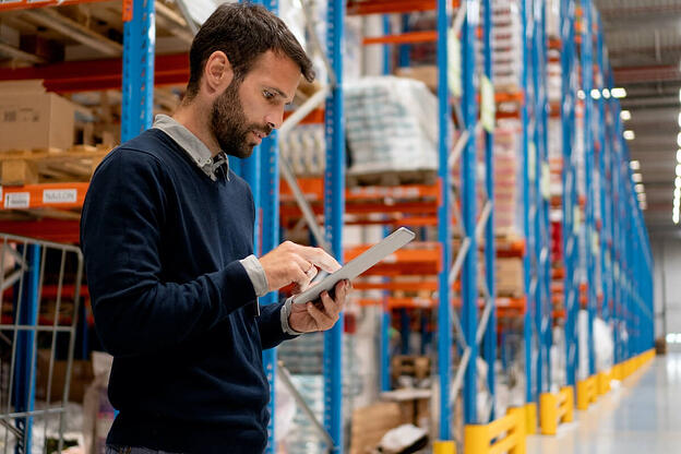 Procurement vs purchasing: A warehouse manager uses a tablet to make a company purchase